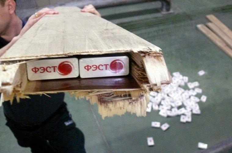 Funkcjonariusz trzyma deskę z widoczną skrytką, w której znajdują się papierosy