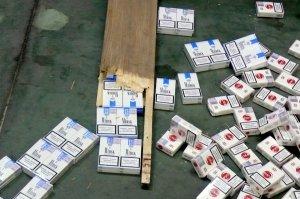 Papierosy na podłodze hali. Obok leżą spreparowane deski